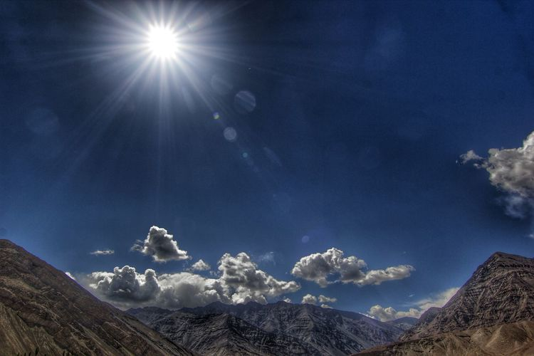 Scenic View Of Mountains Against Blue Sky During Sunny Day