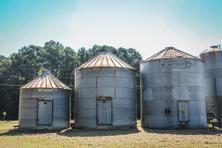 Silos on field against sky
