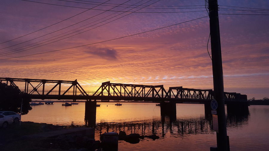 Bridge over sea against dramatic sky