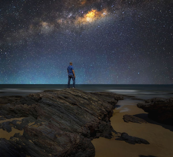 Landscape with Milky Way. Night sky with stars and silhouette of a standing man on the rock at beach. Alone Astronomy Beauty In Nature Constellation Exploration Full Length Galaxy Leisure Activity Milky Way Milky Way Galaxy Nature Night One Person Outdoors People Real People Rock - Object Scenics Sea Sky Space Standing Star - Space Stars Wallpaper