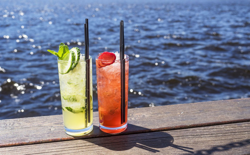 Close-Up Of Drinks On Boardwalk Against Sea