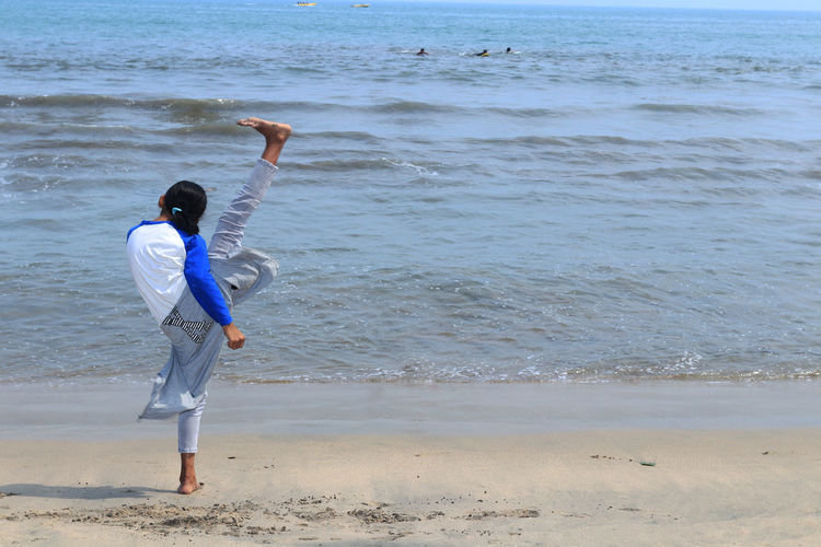 Rear View Full Length Of Girl Doing Martial Arts At Beach