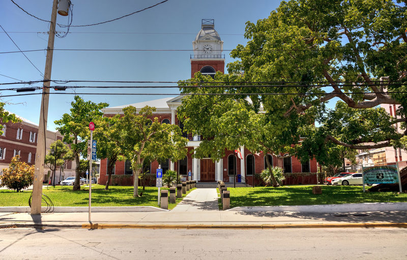 Key West, Florida, USA - September 1, 2018: Monroe County Courthouse with a Large Kapok tree Ceiba pentandra, also called the Ceiba tree, growing in front in Key West, Florida Architecture Ceiba Pentandra Ceiba Tree Government Building Historical Building Kapok Tree Monroe County Courthouse Old Town Old Town Key West Architecture Building Building Exterior Built Structure Courthouse Day Nature Old Key West Outdoors Plant Sky Tree