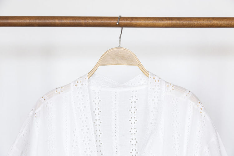 Woman blouse with White blouse linen on wooden hangers. Hanging Coathanger White Color Indoors  Clothing No People Close-up Fashion Focus On Foreground White Background Dress Casual Clothing Wall - Building Feature Still Life Pattern Textile Studio Shot Day Simplicity Ceiling Wood Lace Lace - Textile Handmade Handcraft