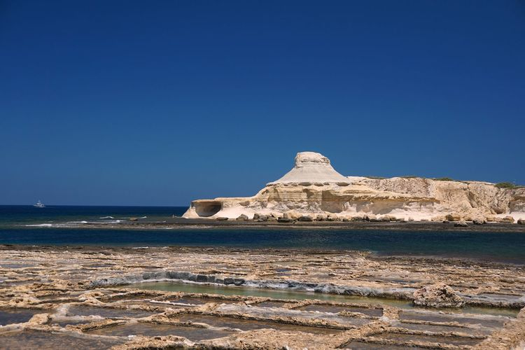 Malta Maltaphotography Malta In My Eyes Gozo Gozo Island Gozo Malta Summer Sky Blue Water Clear Sky Sea Land Scenics - Nature Beauty In Nature Tranquil Scene Nature Copy Space Tranquility Rock Day Rock Formation Beach No People Sunlight Rock - Object Outdoors Stack Rock Arid Climate Eroded