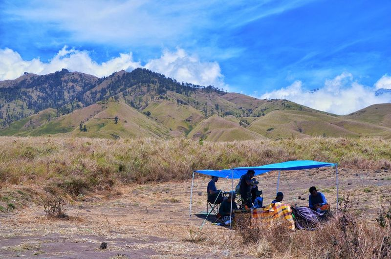 MOUNT RINJANI, LOMBOK INDONESIA. SEPT 16th 2017- Group of tourist take a rest before continue their journey to Mount Rinjani via sembalun route. Good weather with amazing blue sky. Wallpaper Background Hiking INDONESIA Mount Rinjani Sembalun Route Tree Mountain Oil Pump Blue Desert Sky Landscape Mountain Range Cloud - Sky Scenics Tranquility Hiker Hiking Pole Horizon Over Water Sand Dune