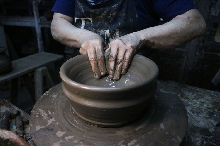 Potter Art And Craft Clay Craft Craftsperson Creativity Expertise Hand Human Hand Indoors  Making Men Mud Occupation One Person Pottery Pottery Art Pottery Pieces Preparation  Real People Skill  Spinning Working Workshop