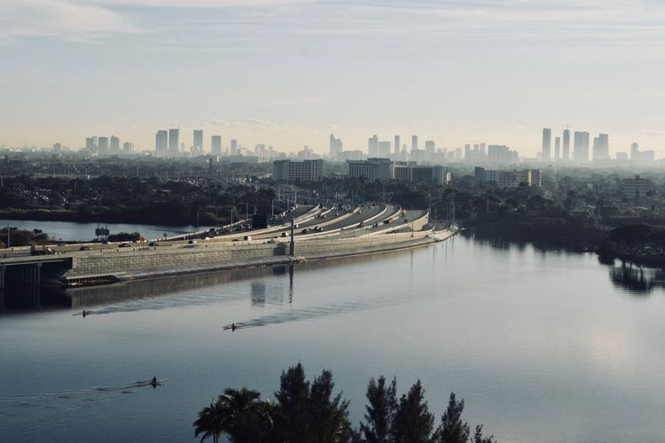 Scenic View Of River By City Against Sky