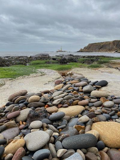 Stones on beach against sky