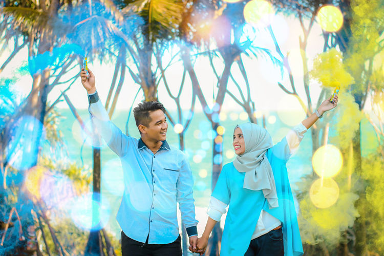 Young couple holding smoke bombs while standing in park