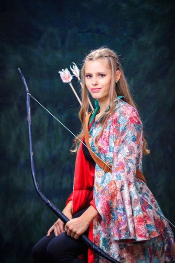 Portrait of smiling teenage girl holding bow and arrow