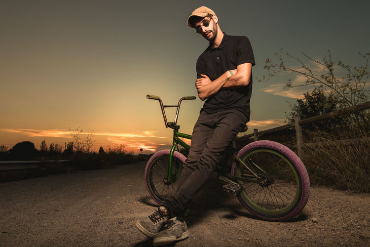 Young man riding bicycle on street against sky during sunset