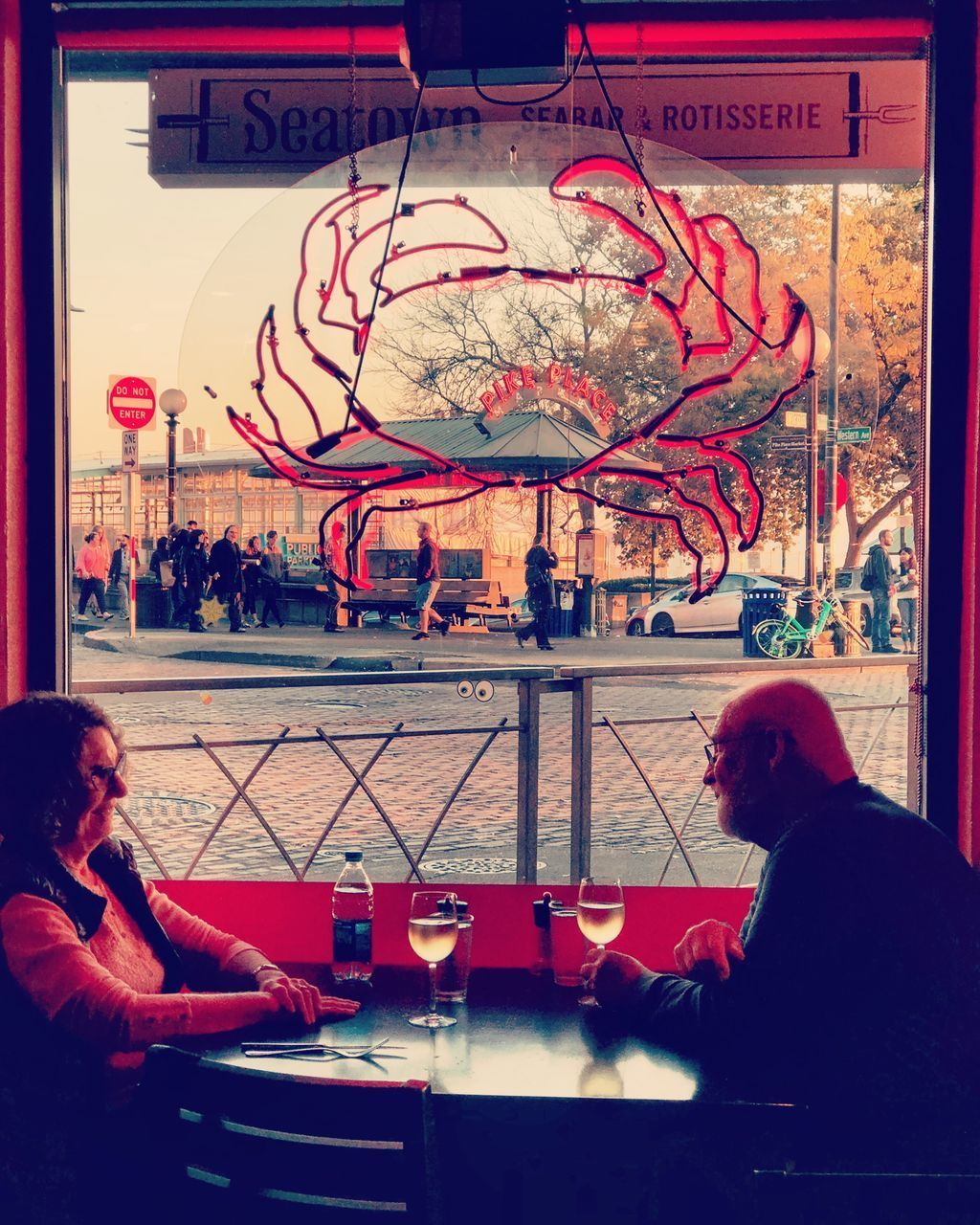 REAR VIEW OF MAN AND WOMAN SITTING AT RESTAURANT