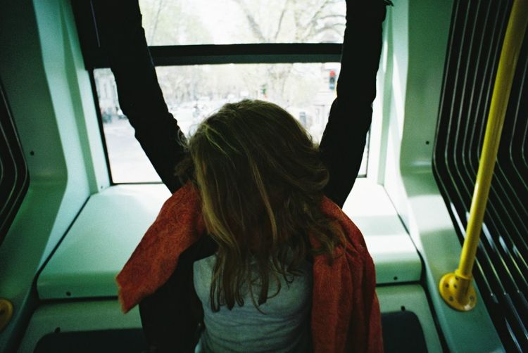 Woman hanging on the tram inside