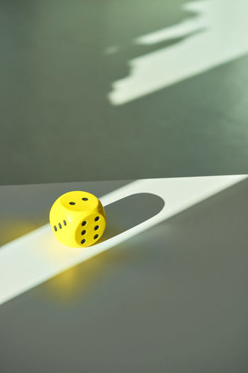 High Angle View Of Yellow Dice On Table