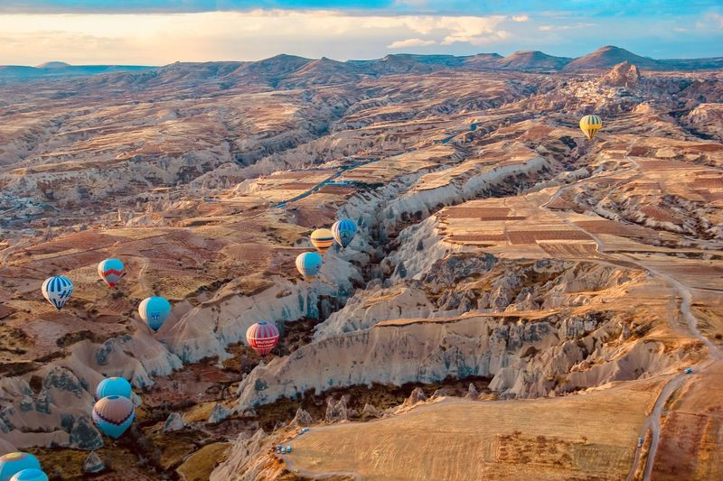 Balloons over Cappadocia Hot Air Ballooning EyeEm Selects Environment Nature Sky No People Day Landscape Beauty In Nature Mountain Scenics - Nature Land Cloud - Sky Outdoors Tranquil Scene Tranquility Sunlight High Angle View Rock Solid Rock - Object Travel