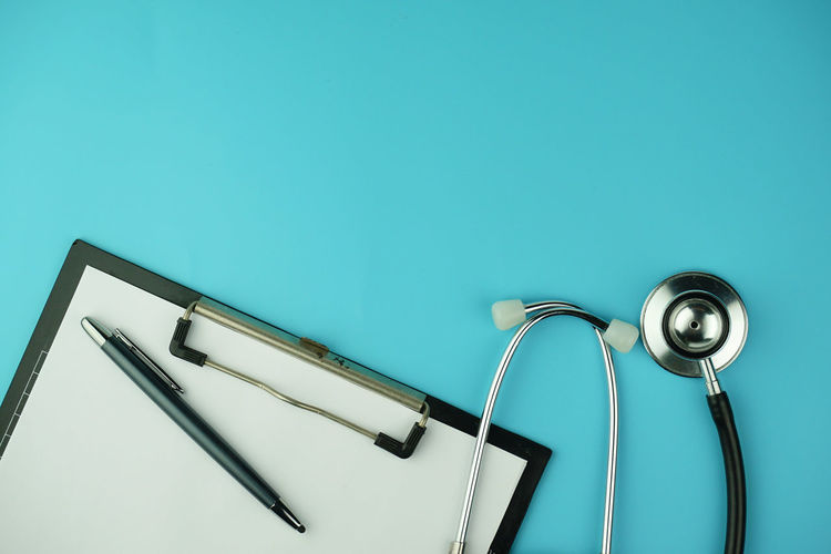 Directly above shot of clipboard and stethoscope on blue background