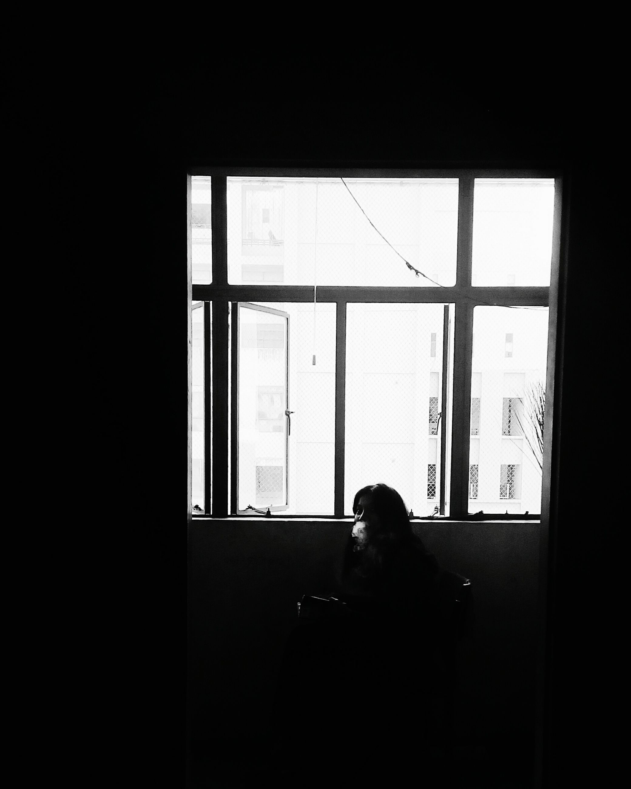 indoors, window, men, glass - material, rear view, transparent, waist up, sitting, silhouette, looking through window, dark, domestic life, day, casual clothing, darkroom, young adult, one mid adult man only