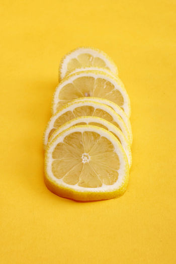 Sliced lemon isolated on color background Citrus Fruit Yellow Fruit Studio Shot Food Food And Drink Healthy Eating Colored Background Wellbeing SLICE Indoors  Yellow Background Lemon Freshness Cross Section No People Close-up Single Object Orange Color Orange