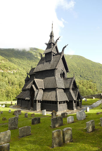 Borgund Stave Church (Stavkirke) in Norway. Vertical format. Architecture Borgund Building Exterior Built Structure Cemetery Church Day Grass Graveyard Mountain Nature No People Nordic Norway Outdoors Religion Scandinavia Scandinavian Stave Church Stavkirke Temple Tomb Tombs Tombstone Tourism