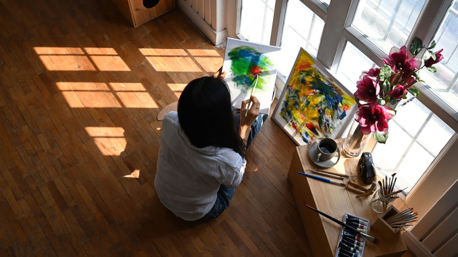 High angle view of woman painting in book while sitting on hardwood floor at home