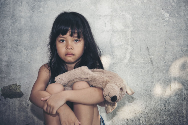 Portrait of cute girl with toy against wall