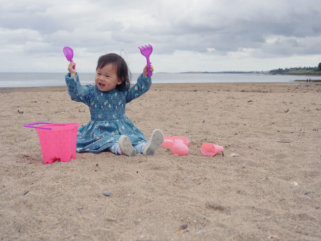 baby playing at sandy beach,Northern Ireland Asian Baby Girl Beach Casual Clothing Childhood Cloud - Sky Cute Day Full Length Girls Happiness One Person Outdoors People Pink Color Playing Real People Sand Sand Pail And Shovel Sea Sky Smiling Water
