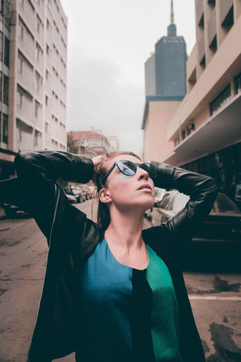 Young woman wearing sunglasses standing against buildings in city