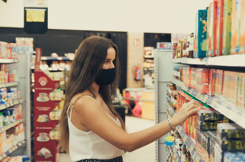 Girl with a face mask buying items at the supermarket.