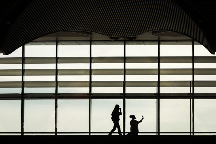 Silhouette people walking at airport