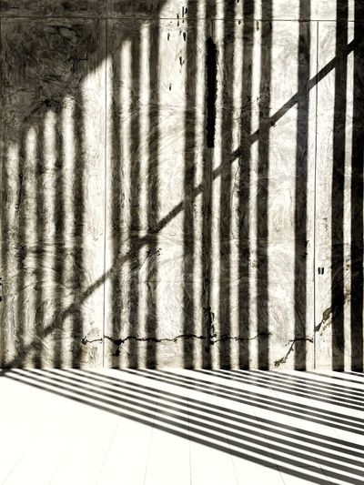 Shadow of metal fence on wall