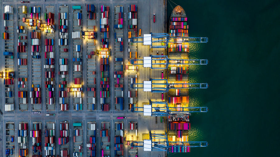 Aerial view container ship loaded in container terminal at night, global business import export