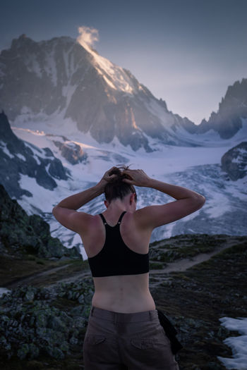 Rear view of woman tying hair while standing against mountain during winter