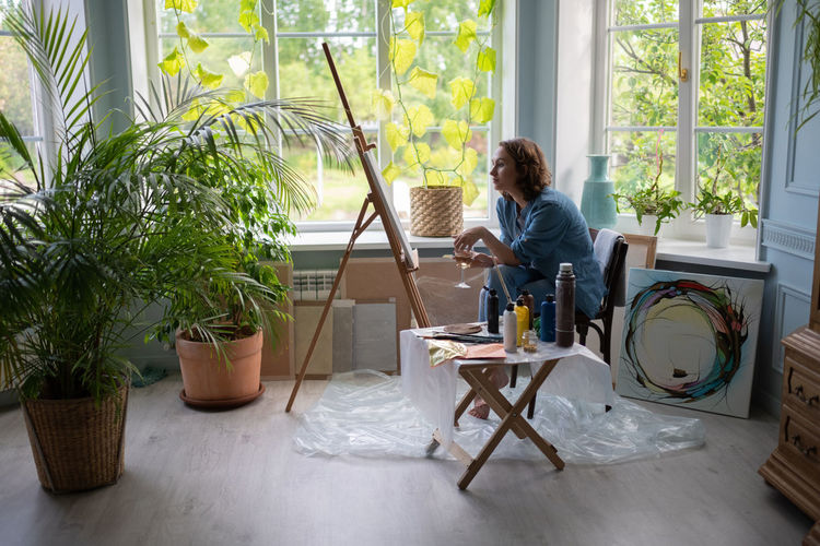 Woman sitting on table by potted plants