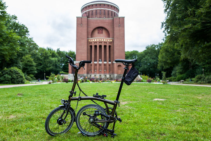 Brompton Black Lacquer edition in Hamburg Brompton Architecture Bicycle Building Exterior Built Structure Day Field Focus On Foreground Grass Green Color Growth Land Vehicle Lawn Nature No People Outdoors Park Park - Man Made Space Plant Transportation Tree