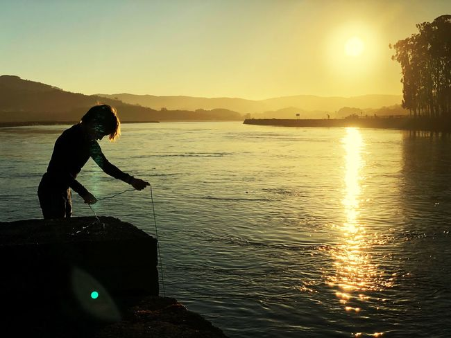 Fishing Sunset Water Silhouette One Person Sea Nature Mountain Beauty In Nature One Man Only Adventure People Outdoors Scenics Sky Day Men Full Length Real People Side View Standing