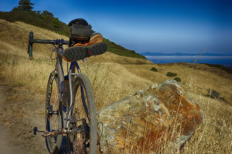 Adventure Adventure Time Beauty In Nature Bicycle Bicycles Blue Day Dirt Road Dirt Road Riding Dry Grass Field Grass Land Vehicle Landscape Mountain Mountain Bike Nature No People Outdoor Activity Outdoor Pursuit Outdoors Scenics Sky Transportation