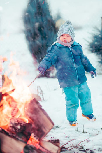 Boy playing a stick by campfire outdoors in the winter. Kid wearing warm clothes, scarf and wool cap Winter Child Outdoors Childhood Boy Girl Cold Enjoyment Enjoy Kid Children Wintery Winter Snow Snowing Picnic Family Eating Campfire Roasting Marshmallows Snack Roasted Spending Time