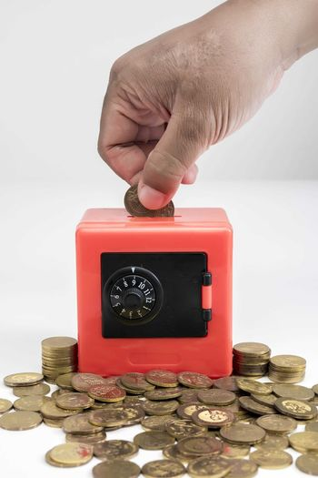 Hand holding coins and put into red safe box Human Body Part Human Hand Coin Hand Indoors  Currency Wealth Red One Person Real People Finance Human Finger Finger Studio Shot Savings Holding Large Group Of Objects Unrecognizable Person Body Part Economy