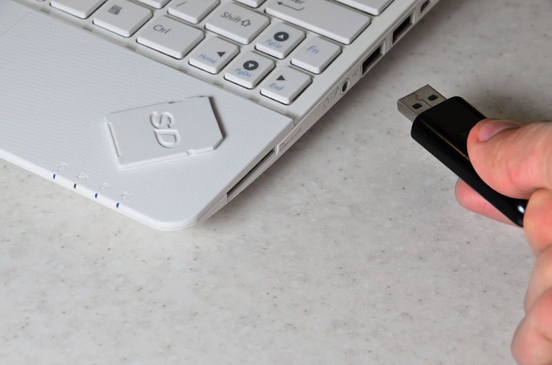 Cropped hand inserting usb stick to laptop