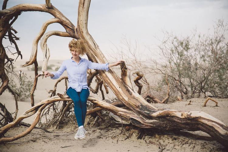 Woman on dead tree