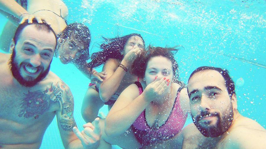 Portrait Of Happy Friends Swimming In Pool