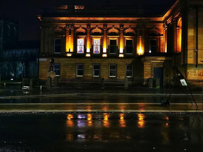 Illuminated building by wet street during rainy season at night