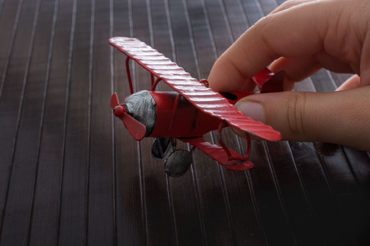 Cropped hand holding toy airplane on table