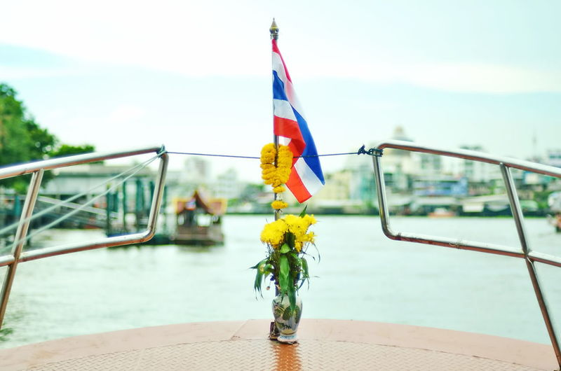 Close-up of thai flag with flowers on sailboat in river