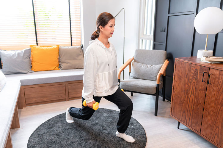 Full length of woman sitting on sofa at home