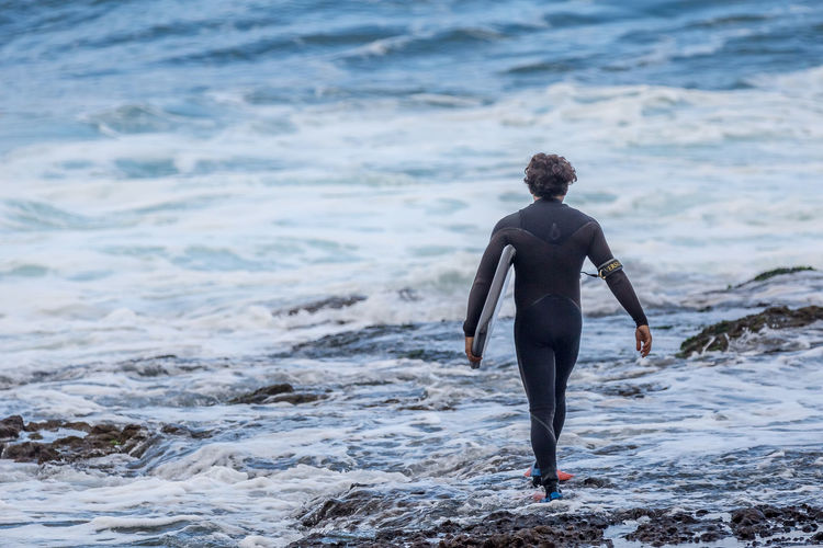 Rear View Full Length Of Man In Wetsuit Holding Surfboard At Sea