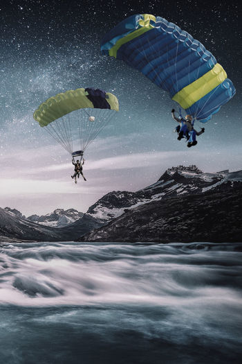 People paragliding in water against sky