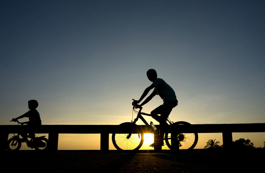 Activity Bicycle Clear Sky Cycling Dusk Full Length Land Vehicle Leisure Activity Lifestyles Men Mode Of Transportation Nature Outdoors People Real People Riding Silhouette Sky Sport Sunset Transportation Two People