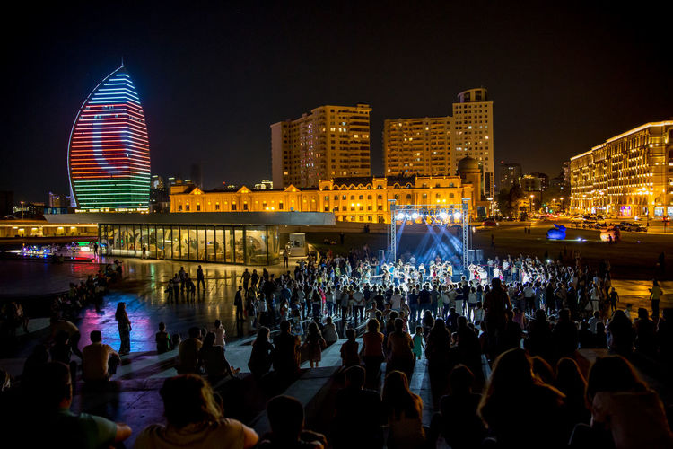 Crowd at illuminated city against sky at night